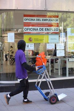 Un joven pasa delante de una oficina de empleo
