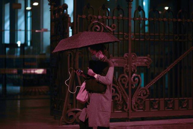 Una persona camina bajo un paraguas.