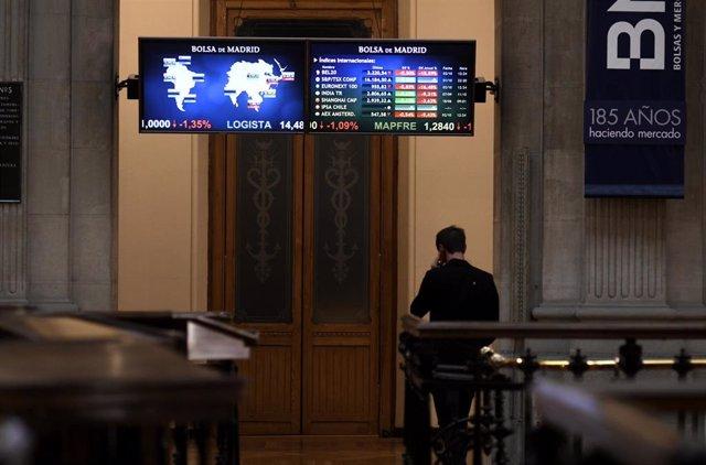 Una persona camina bajo los televisores indicativos con los valores del Ibex en el Palacio de la Bolsa de Madrid (España), a 2 de octubre de 2020.