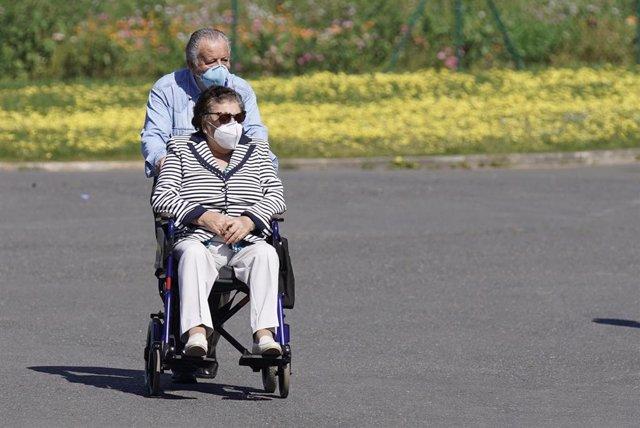 Un hombre empuja a otro en silla de ruedas
