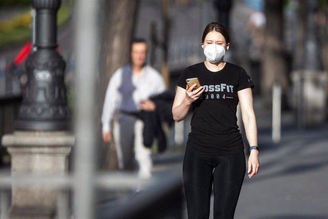 Una mujer con mascarilla utilizando el teléfono móvil