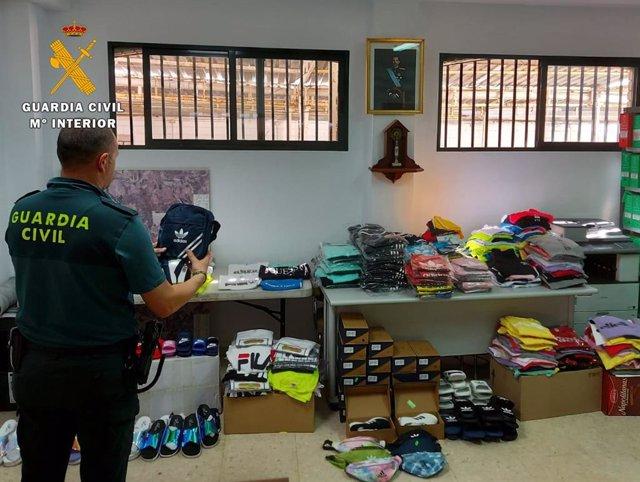 Un agente de la Guardia Civil junto a la ropa intervenida