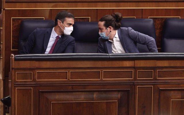 El president del Govern, Pedro Sánchez (i); i el vicepresident segon del Govern, Pablo Iglesias, mantenen una conversa durant la segona sessió del ple en el qual es debat la moció de censura plantejada per Vox.