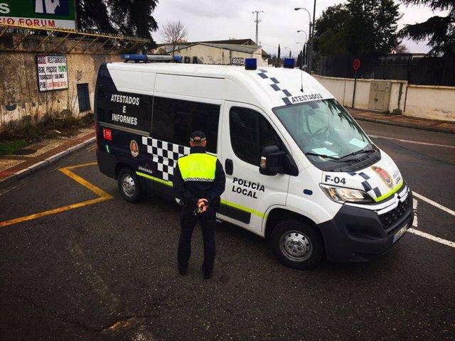 Agente de la Policía Local de Granada junto a un furgón en una foto de archivo