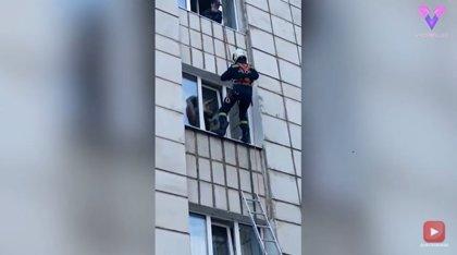 En Perm, Rusia, un bombero se cuelga por la fachada de un edificio para rescatar a un gato atascado en una ventana