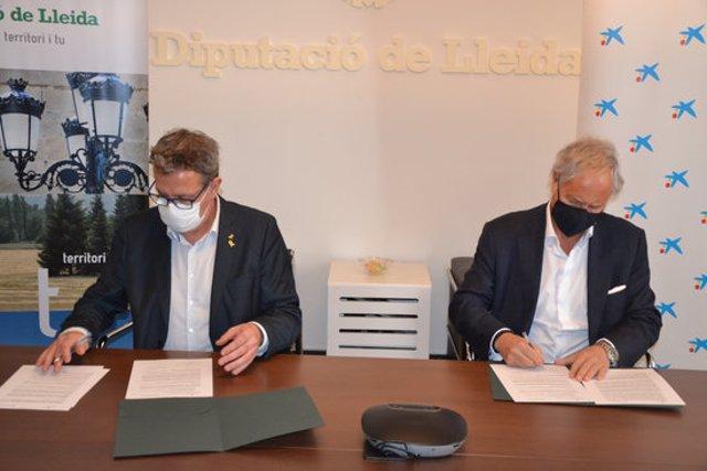 Pla mitjà del president de la Diputació de Lleida, Joan Talarn, i el director de Banca d'Institucions de CaixaBank i director territorial de Catalunya, Joaquim Macià, signant el conveni de col·laboració, el 27 d'octubre del 2020. (Horitzontal)
