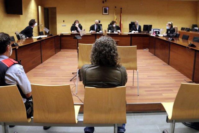 D'esquenes, l'acusat d'agafar la targeta a un amic mentre dormia per treure diners de caixers. Foto del judici del 27 d'octubre del 2020 (horitzontal)