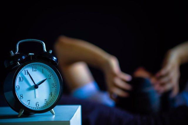 Hombre con insomnio y reloj despertador.