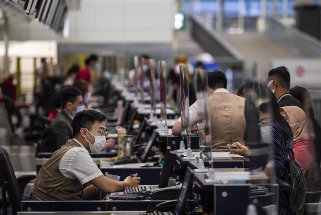 Control de pasaportes y facturación en el aeropuerto de Hong Kong.