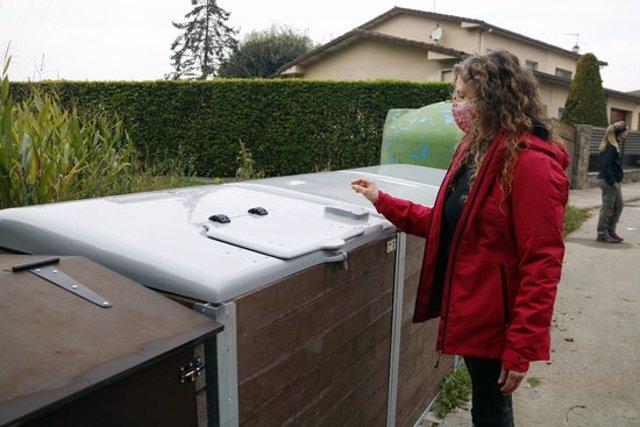 Pla general d'una veïna de Les Masies de Roda (Osona) obrint el compostador el 28 d'octubre del 2020. (horitzontal)