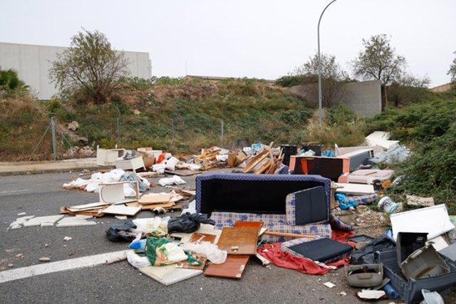 Pla obert d'una zona plena de deixalles i andròmines que ha esdevingut un petit abocador en un carrer sense sortida al polígon de Valls. Imatge del 27 d'octubre del 2020. (Horitzontal)