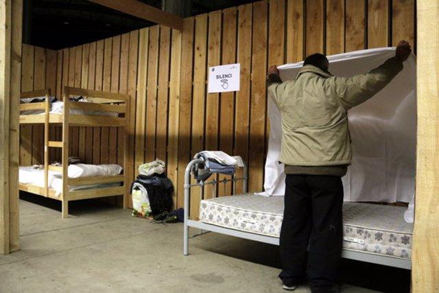 Un els usuaris del Palau de Fires de Girona, l'espai habilitat per l'Ajuntament per als sensesostre, preparant un dels llits. Foto publicada 28 d'octubre del 2020 (horitzontal)