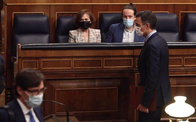 El presidente del Gobierno, Pedro Sánchez, pasa por delante de vicepresidenta primera del Gobierno, Carmen Calvo, y vicepresidente segundo del Gobierno, Pablo Iglesias, durante una sesión de control al Gobierno en el Congreso, en Madri, a 28 de octubre
