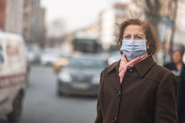 Mujer mayor con mascarilla en una calle con contaminación.
