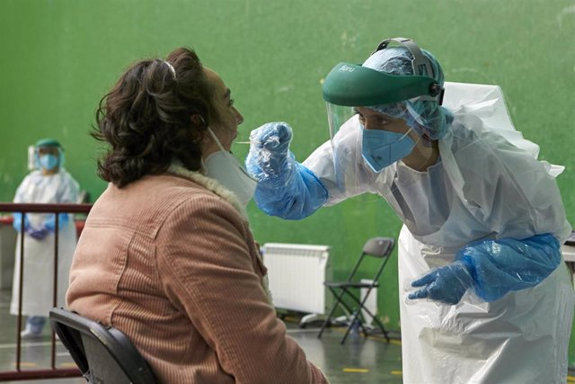 Un sanitario toma muestras a una mujer para realizar una PCR