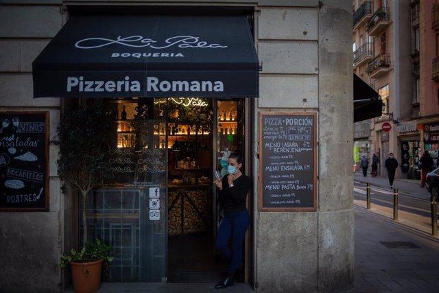 Una trabajadora observa las inmediaciones de su establecimiento de Barcelona, Catalunya (España), tras la paralización de la actividad durante dos semanas en bares restaurantes, el 16 de octubre del 2020.
