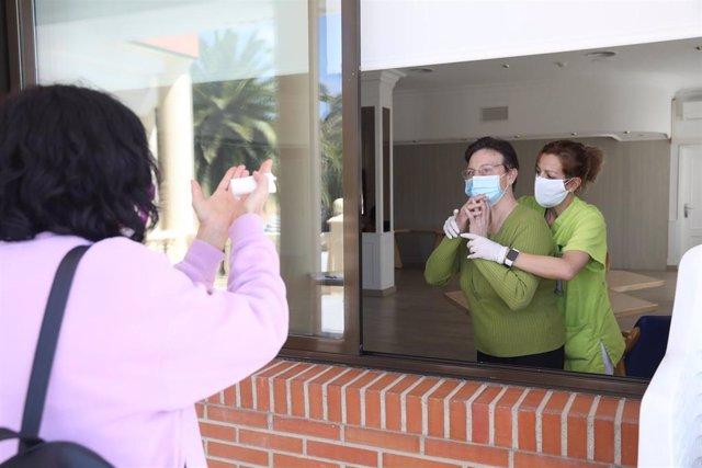 Una residente se comunica con un familiar por una ventana de una residencia.