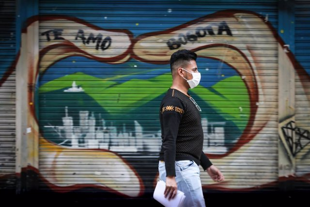 10 March 2020, Colombia, Bogota: A man wearing a surgical mask walks through the