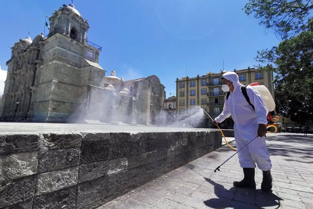 31 August 2020, Mexico, Oaxaca: Aworker wearing a protective suit disinfects th