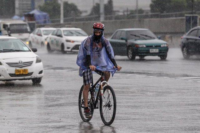 Un hombre circula en bicicleta por Manila bajo las lluvias del tifón 'Molave'