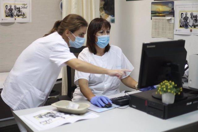 La responsable de enfermería del Centro de Salud Barrio del Pilar, Elisa Varona (d), y la enfermera Elena Mayan trabajan en el Centro de Salud Barrio del Pilar donde vacunan a pacientes contra la gripe, en Madrid, a 14 de octubre