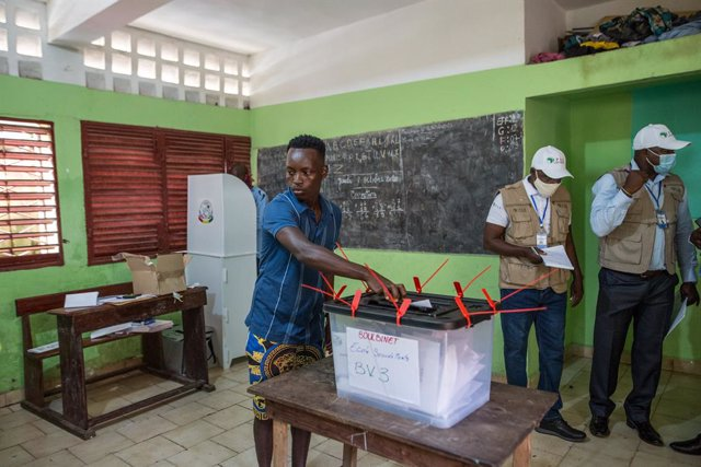 18 October 2020, Guinea, Conakry: A man casts his vote inside a polling station