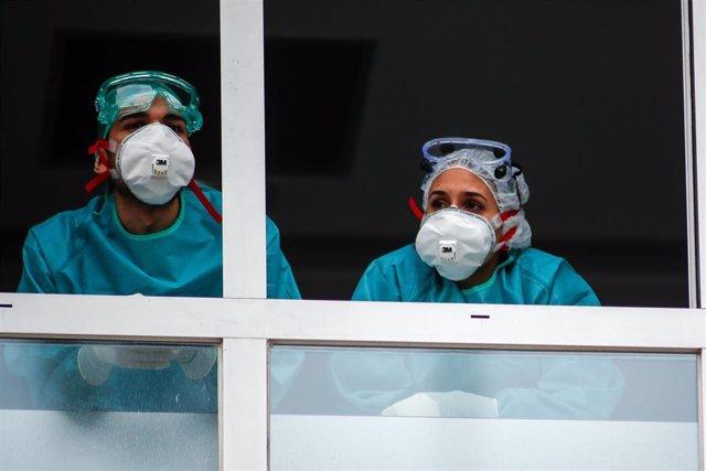 Varios sanitarios con protección EPI, mascarillas, gafas y guantes, observan desde la ventana el homenaje a los Sanitarios celebrado en el Hospital Fundación Jiménez Díaz durante la pandemia de Covid-19 en Abril 21, 2020 in Madrid, España