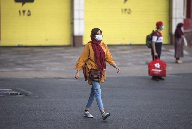 Una mujer con mascarilla en Teherán