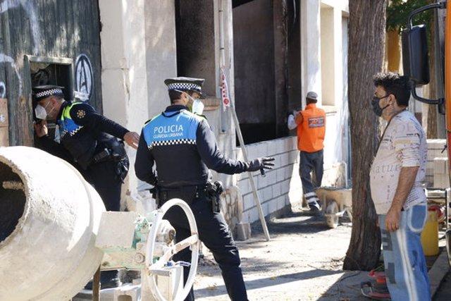 Agents de la Guàrdia Urbana de Reus, conversant amb un ocupa que vivia en unes naus de la ciutat, on hi ha hagut un incendi sense ferits i l'Ajuntament ha ordenat tapiar. Imatge del 29 d'octubre del 2020. (Horitzontal)