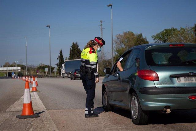 Una agente de Mossos d'Esquadra en un control en el peaje de La Roca del Vallès pide a un conductor el justificante que le permite su salida de casa durante el estado de alarma, en La Roca del Vallès (Barcelona), 9 de abril de 2020.