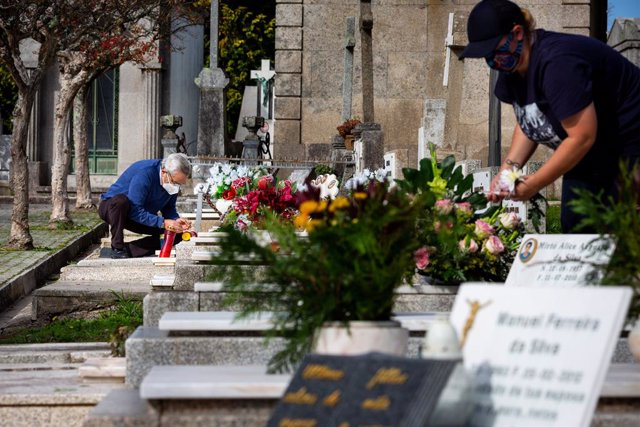 28 October 2020, Portugal, Porto: People wearing face masks are seen cleaning the graves at Agramonte cemetery before the National Day of All Saints. People are still allowed to visit the cemetery before the National Day of All Saints to pay tribute to th