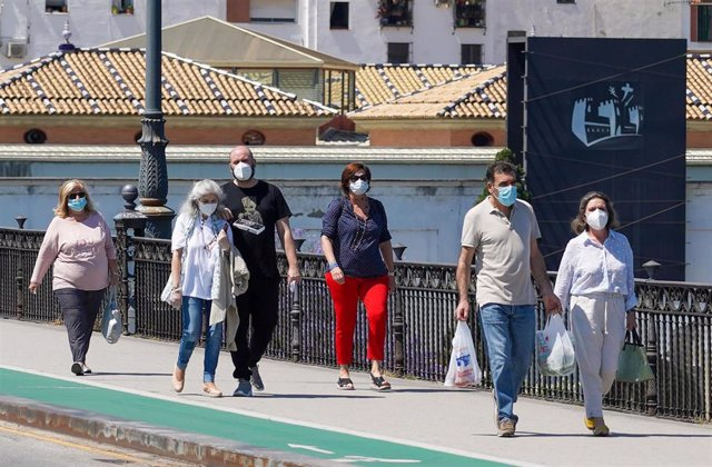 Ciudadanos paseando por el puente de triana  en el  primer día del uso obligatorio de mascarillas por el Covid-19. Sevilla a 21 de mayo del 2020