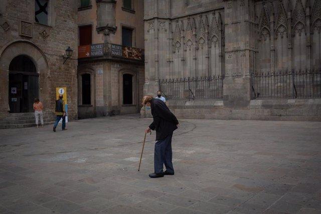 Un anciano camina por una plaza del Barrio Gótico una semana después de la entrada de las nuevas restricciones en Cataluña, en Barcelona, Catalunya(España) a 23 de octubre de 2020. El pasado viernes 16 de octubre entraron en vigor las nuevas restricciones