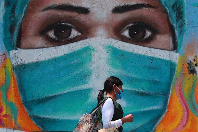 Una mujer en México frente a un mural de agradecimiento a la labor del personal sanitario durante la pandemia del coronavirus.