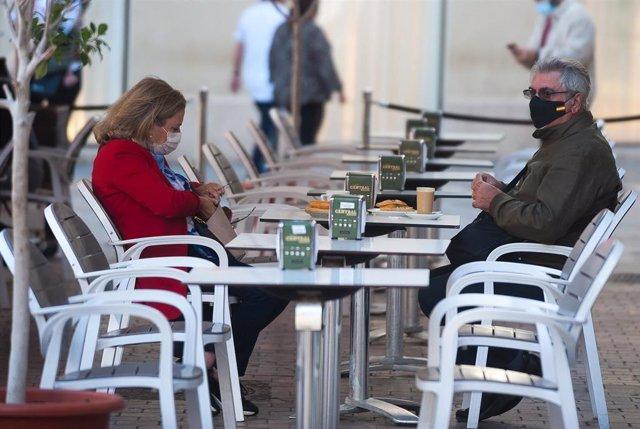 Consumidores de terrazas, bares y cafeterías de Málaga portan sus mascarillas ante la obligatoriedad  por parte de la Junta de Andalucía de ponérselas  mientras no se esté consumiendo. Málaga a 26 de octubre 2020
