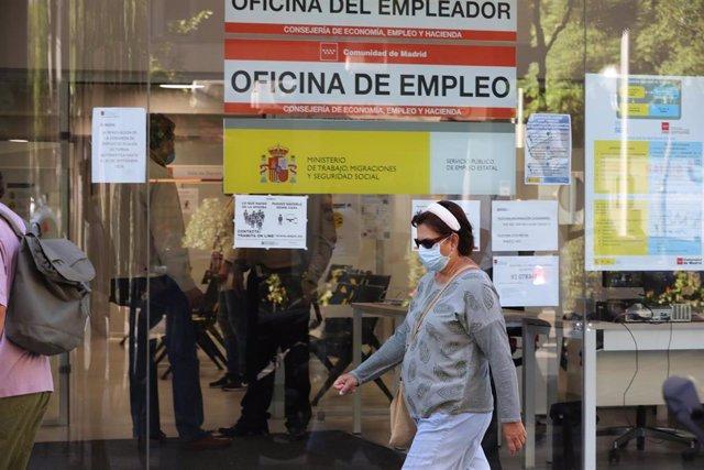 Una mujer con mascarilla pasa por una oficina de empleo de Madrid