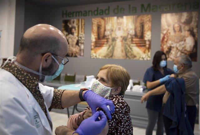 Dos personas se vacunan en la Casa de Hermandad de la Macarena, durante la administración de vacunas contra la gripe a personas mayores de 65 años, foto de archivo