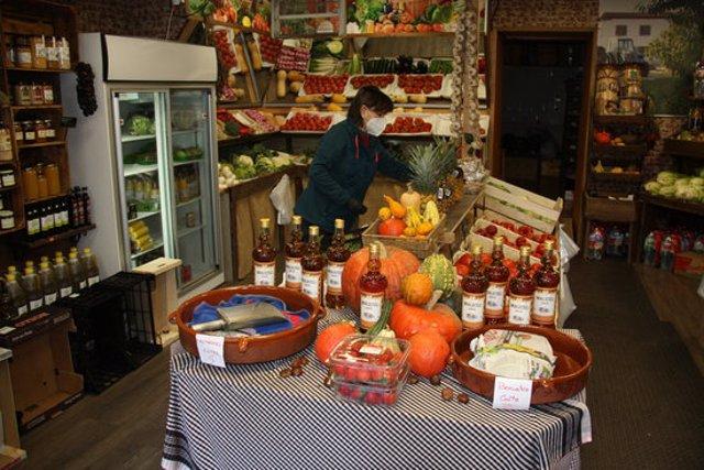 Pla obert de la propietària d'una fruiteria de Bellver de Cerdanya endreçant el gènere en el primer dia de confinament municipal de caps de setmana. Imatge del 30 d'octubre de 2020 (Horitzontal).