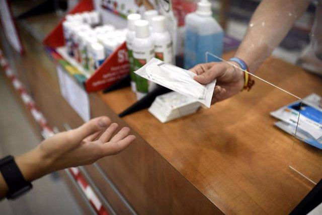 Un farmacéutico entrega a un cliente una de las mascarillas KN95 que ha recibido en su farmacia, en Madrid (España), a 30 de septiembre de 2020.
