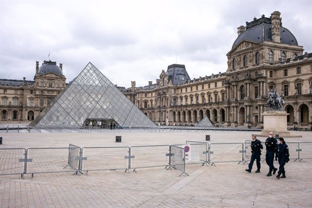 30 October 2020, France, Paris: Police officers walk in front of the closed Louvre museum, as France goes into coronavirus lockdown for the second time this year from today, Friday, until 1 December 2020 to curb the spread of the coronavirus pandemic. Pho