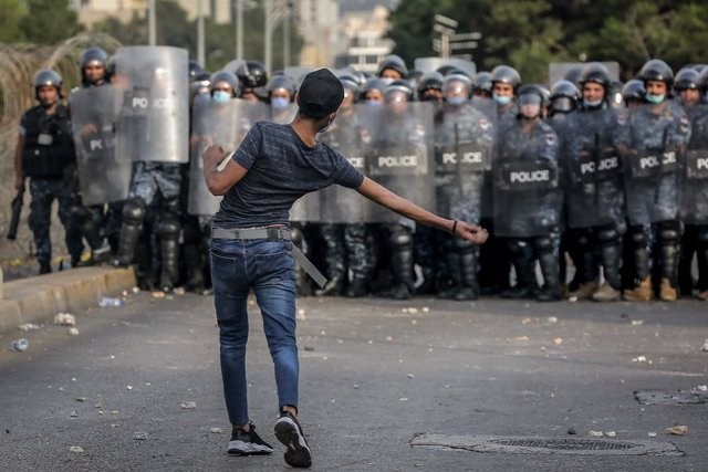 30 October 2020, Lebanon, Beirut: A protester throws stone at riot police protecting the residence of the French ambassador in Beirut, during a demonstration against French President Emmanuel Macron's comments on Islam's prophet Muhammad cartoons. Photo: