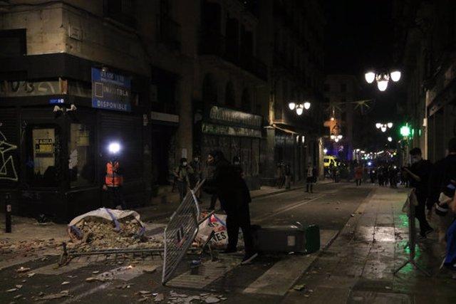 Restes de runa i tanques de seguretat per terra en un carrer de Barcelona després d'una concentració de persones contràries a les restriccions per la covid-19. 30 d'octubre del 2020. Pla general. (Horitzontal)