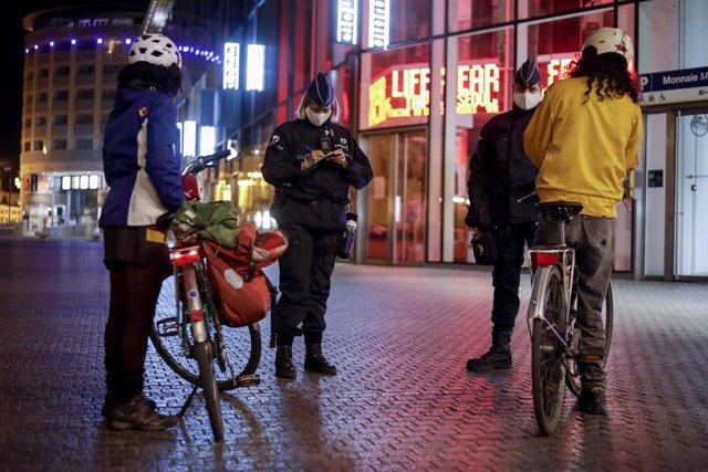 Policía belga habla con ciudadanos durante el toque de queda impuesto en Bélgica por la pandemia de coronavirus.