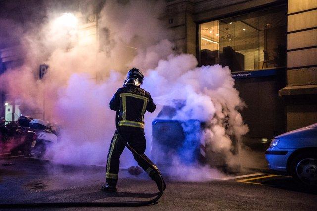 Un bombero apaga un fuego en un cubo de basura quemado por manifestantes durante una protesta por las restricciones por el COVID-19