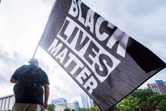 24 August 2020, US, Charlotte: A Black Lives Matter supporter waves a flag during a protest on the opening day of the Republican National Convention. Photo: Sean Meyers/ZUMA Wire/dpa