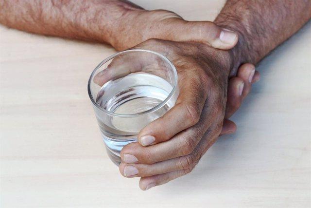 Hombre se sujeta la mano que tiembla mientras sostiene un vaso.