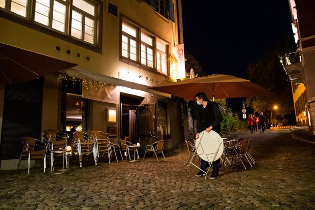 30 October 2020, Baden-Wuerttemberg, Freiburg im Breisgau: A worker of a cocktail bar carries a table in the outdoor area of his bar before closing time. Germany's federal and state governments agreed on last Wednesday to sweeping contact restrictions and