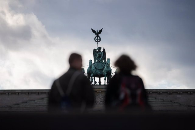 24 October 2020, Berlin: Two passers-by stand in front of the Brandenburg Gate. Photo: Christoph Soeder/dpa
