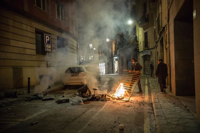 30 October 2020, Spain, Barcelona: A man puts a barrier near burning trashes laid by protesters during a protest against the government's Coronavirus restrictions. Photo: Thiago Prudêncio/SOPA Images via ZUMA Wire/dpa