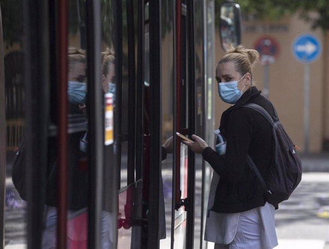 Una pasajera protegida con mascarilla, antes de subir a un autobús Tussam,